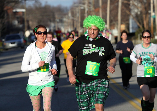 Elaine Harold, left, and her father Bill Harold approach the finish of the annual Leprechaun Run in downtown Jeffersonville on Tuesday night. Staff photo by C.E. Branham