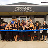 Local business and community leaders stand with the owners and employees of Strandz Salon & Threadz Boutique in front of the business along Vincennes Street in New Albany during an honorary ribbon cutting ceremony at their 20th anniversary celebration on Tuesday evening. Sisters Julie Young, Stefanie Griffith and Stacy Tunnell started the business when they bought Beauty World from their parents in 1993. Staff photo by Christopher Fryer