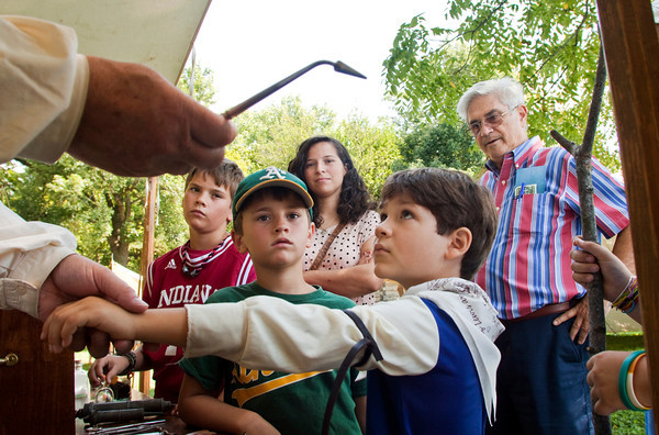 From left, Zach, 11, Nate, 7, and Katelyn Gardner, 15, all of Jeffersonville, look on with their grandfather, Sam Gardner, of Clarksville, as living history interpreter Edwin Eller, of St. Charles, Mo., uses Simon Khan, 7, of Louisville, to demonstrate the amputation process while discussing medical practices from the 19th century at the annual Lewis and Clark Heritage Trail meeting at the George Rogers Clark Home Site in Clarksville on Saturday afternoon. Staff photo by Christopher Fryer