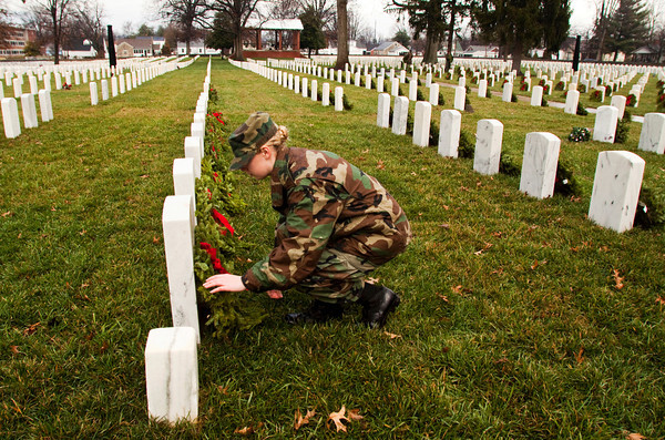 Civil Air Patrol cadet Samantha Morgan, of the Indiana Wing's Falcon Composite Squadron, places a wreath on a soldier's grave at the New Albany National Cemetery on Saturday afternoon. Members of the squadron held a ceremony and placed more than 750 wreaths around the cemetery to honor veterans for the holiday season as part of Wreaths Across America. Staff photo by Christopher Fryer