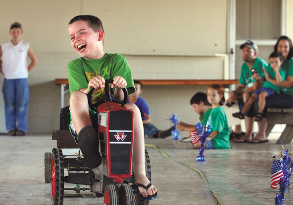 Landon Hall lets out a laugh as he finishes his ride in the Clark County 4-H Fair children's tractor pull Sunday afternoon. More than forty kids participated in the annual event. Staff photo by C.E. Branham
