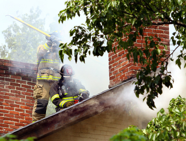 Jeffersonville firefighters ventilate the roof of a two-story apartment building that caught fire Tuesday afternoon in the 900 block of East Maple St. No occupants or firefighters were injured. Staff photo by C.E. Branham