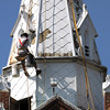 A worker with D M Masonry, suspended in a bosun's chair, begins restoration work on the steeple of First Presbyterian Church in Jeffersonville. The complete project, involving a three-color paint scheme to bring out architectural detail, should be completed in 4-6 weeks according to Pastor Don Summerfield. Staff photo by C.E. Branham