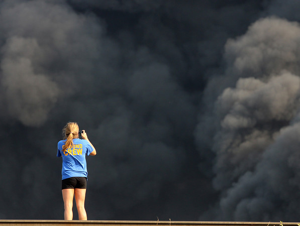A onlooker films a huge fire Saturday evening at Riverside/QRS Recycling in New Albany. Staff photo by C.E. Branham