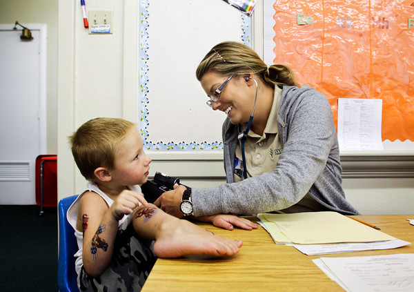 Gavin Toops, 4, of New Albany, shows off his temporary tattoos while Ivy Tech Community College nursing student Bobbie Kraft, of New Albany, takes his blood pressure during preschool assessments at Floyd County Head Start in New Albany on Wednesday afternoon. Twenty one nursing students were on hand to perform eye examinations, analyze dental and vaccination records, test speech, and measure height, weight and blood pressure to assess income eligible, three, four and five-year-old Floyd County residents applying to be accepted for one of the 276 openings in the preschool program. Staff photo by Christopher Fryer