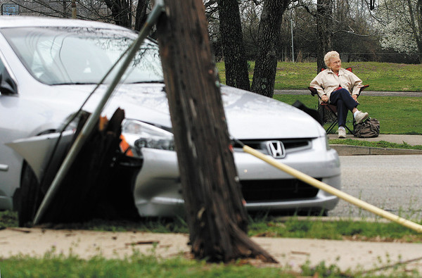 Floris Seabrook, of New Albany, looks on as utility and emergency crews manage the scene of an accident that she was involved in at the intersection of Greenvalley Road and Gordan Drive in New Albany on Friday afternoon. No one was injured in the accident. Staff photo by Christopher Fryer