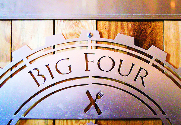 A Big Four Burgers + Beer logo sign hangs below a counter in a dining room at the Jeffersonville restaurant. Staff photo by Christopher Fryer
