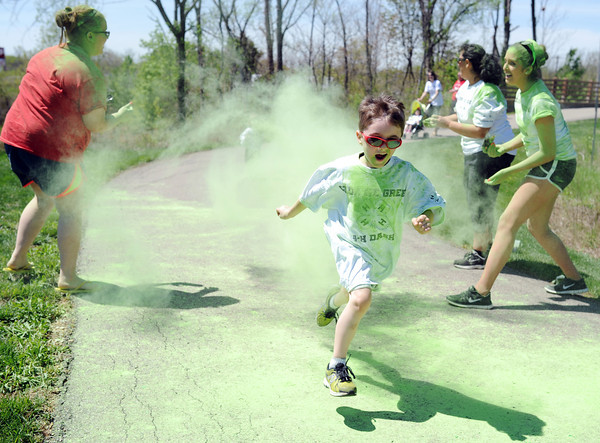 A One Mile Color Fun Run participant emerges from a cloud of green pigment during the YMCA's Healthy Kid Day and Purdue Extension's Spring Festival Saturday afternoon. The free community event was geared to inspire kids to their minds and bodies active.<br /> Staff photo by Tyler Stewart