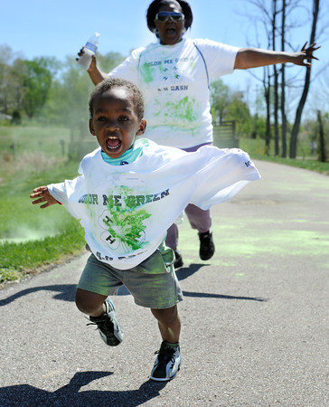 Participants run away from the green pigment dust during the One Mile Color Fun Run, as part of the nationwide YMCA's Healthy Kid Day at the Purdue Extension in New Albany Saturday morning. The Healthy Kid day is celebrated at nearly 1,600 YMCA's across the country.<br /> Staff photo by Tyler Stewart