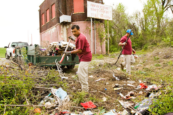 Juan Martinez, left, and Jose Velazquez, both with Walnut Ridge Landscaping, work to clean up an illegal dumping site next to an old water intake station on property owned by Indiana American Water along West Water Street in New Albany. Staff photo by Christopher Fryer