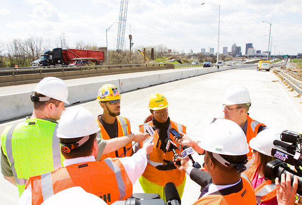 Walsh Construction flaggers Vincent Groves, center left, and Engua Kuku, center right, speak with members of the media on a temporary bridge along Interstate 71 during a tour of the Ohio River Bridges Project as part of National Work Zone Awareness Week in Louisville on Wednesday afternoon. Staff photo by Christopher Fryer