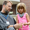 Friar John Bamman and Siobahn Powell, 6, Corydon, work together to create a friendship bracelet at a booth during the annual Mount Saint Francis Center for Spirituality Picnic Saturday afternoon. The picnic offered booths with free activities for families to enjoy as they walked the grounds of Mount Saint Francis. <br /> Staff photo by Tyler Stewart