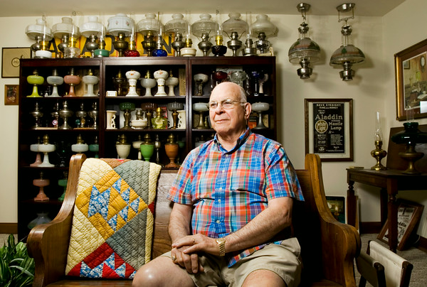 Bill Lohmeyer sits in front of part of his Aladdin kerosene lamp collection in his New Albany home on Tuesday morning. Lohmeyer, a retired attorney, started collecting the lamps more than 35 years ago, and currently owns about 300, some of which date back more than 100 years. Staff photo by Christopher Fryer