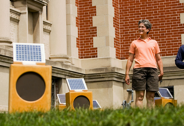 "Stephanie Warren, Floyds Knobs, smiles as she listens to music generated by solar-powered sound boxes as part of the installation ""Sun Boxes"" on the front lawn of the Carnegie Center for Art and History in downtown New Albany on Friday afternoon. The piece was created by sound artist Craig Colorusso, Rogers, Ark., and each box is activated and powered by direct sunlight, and each one generates a single note that Colorusso originally recorded with an electric guitar. Once all the boxes are active they form a B flat six chord, which contains four notes. Five boxes are committed to each of the four notes, with 20 boxes total in the installation. Colorusso has taken the portable installation to 19 states since 2009, and plans to make stops in all 50. Staff photo by Christopher Fryer"