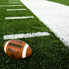 A football is pictured on top of the new artificial playing surface of Gene Sartini Field at Providence High School's Murphy Stadium in Clarksville on Wednesday evening. Providence, New Albany and Floyd Central high schools all had artificial turf installed this summer. Staff photo by Christopher Fryer