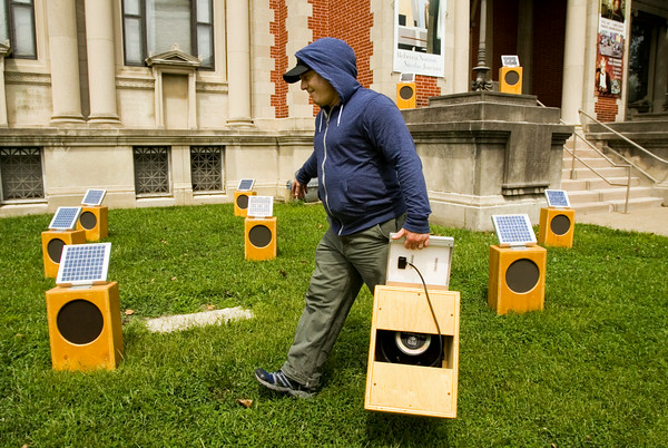 "Sound artist Craig Colorusso, Rogers, Ark., places solar-powered sound boxes around the front lawn of the Carnegie Center for Art and History as part of his installation ""Sun Boxes"" in downtown New Albany on Friday afternoon. The boxes are activated and powered by direct sunlight and each one generates a single note that Colorusso originally recorded with an electric guitar. Once all the boxes are active they form a B flat six chord, which contains four notes. Five boxes are committed to each of the four notes, with 20 boxes total in the installation. Colorusso has taken the portable installation to 19 states since 2009, and plans to make stops in all 50. Staff photo by Christopher Fryer"