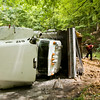 An overturned GEA Inc. dump truck is pictured along the 4000 block of Budd Road in Floyd County on Monday afternoon. The truck overturned while moving downhill in the southbound lane at about 1 p.m. There were no injuries, and no other vehicles were involved in the accident. Staff photo by Christopher Fryer