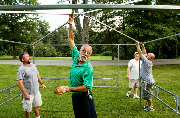 Maintenance Director George Scholl, Jeffersonville, helps volunteers set up booth framework in preparation for the annual picnic at Mount Saint Francis in Floyds Knobs on Tuesday evening. The picnic opens at 11 a.m. and runs to midnight. Staff photo by Christopher Fryer