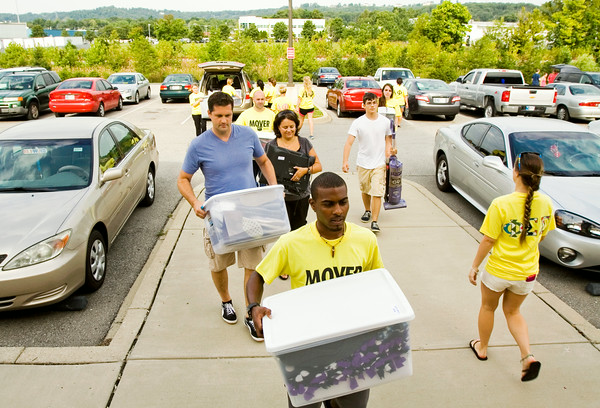 Volunteer movers help the Kaiser family, center left, and other families and students move into Orchard Lodge at Indiana University Southeast in New Albany on Thursday morning. The school has 399 students scheduled to live in the on-campus residence halls. Staff photo by Christopher Fryer
