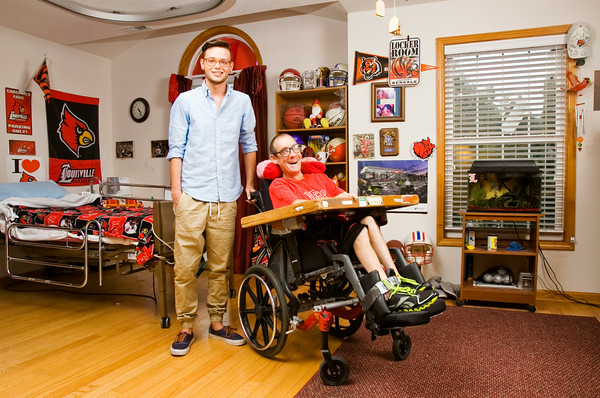 House manager Cole Loney, left, stands with Tim LaDuke, who has cerebral palsy, inside the Volunteers of America run home that LaDuke shares with other disabled adults in New Albany on Tuesday afternoon. LaDuke is one of 72 adult residents on the VOA client list in Southern Indiana. Staff photo by Christopher Fryer