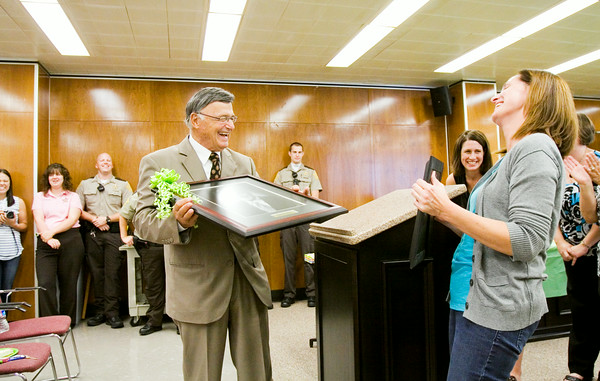 Floyd County Magistrate Daniel Burke is presented with a portrait while holding his official portrait that will be hung in the magistrate courtroom during his retirement reception at the City-County Building in downtown New Albany on Friday afternoon. Staff photo by Christopher Fryer