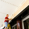 Donnie Richardson, Scottsburg, works on a new section of wooden paneling above the front entrance to The Grand in downtown New Albany on Wednesday afternoon. The work is being done to cover an old lettering board, and a trompe l'oeil artist is scheduled to paint the name of the historic theater on the space. Staff photo by Christopher Fryer
