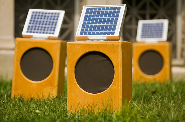 "Solar-powered sound boxes are pictured on the front lawn of the Carnegie Center for Art and History as part of the installation ""Sun Boxes"" in downtown New Albany on Friday afternoon. The piece was created by sound artist Craig Colorusso, Rogers, Ark., and each box is activated and powered by direct sunlight, and each one generates a single note that Colorusso originally recorded with an electric guitar. Once all the boxes are active they form a B flat six chord, which contains four notes. Five boxes are committed to each of the four notes, with 20 boxes total in the installation. Colorusso has taken the portable installation to 19 states since 2009, and plans to make stops in all 50. Staff photo by Christopher Fryer"