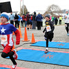 Aaron Lord, 9, along with his twin brother, Aidan, cross the finish line in their super hero athletic wear during Fast Freddie's Festive Five-Mile Foot Feast at the Floyd County 4-H fairgrounds Thursday morning in New Albany. <br /> Staff photo by Tyler Stewart