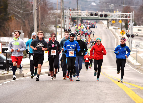 Runner make their way up an incline on Mt. Tabor Road as they head toward Grant Line Road about a mile and a half into Fast Freddie's<br /> Festive Five-Mile Foot Feast Thursday morning in New Albany. More than 900 runners had pre-registered as of race day, despite an overnight snow.<br /> Staff photo by Tyler Stewart
