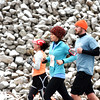 Runners pass a wall of rocks dusted with snow as they head down hill on Mt. Tabor Road before turning onto Grant Line Road two miles into the Fast Freddie's Festive Five-Mile Foot Feast. Over 900 runners pre-registered to participate in the 26th annual run. <br /> Staff photo by Tyler Stewart