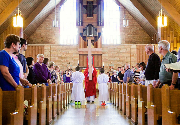 The Rev. Eric Johnson, New Albany, is accompanied by Shea, right, and Sammy Taylor, both of Memphis, during the cross procession at the Our Lady of Perpetual Help Catholic Church's Good Friday service in New Albany on Friday afternoon. Staff photo by Christopher Fryer