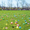 Easter eggs fill a baseball field after being dropped from a helicopter, while the 1 to 4 year old hunting group wait along the fence for the countdown to begin.<br /> Staff photo by Tyler Stewart