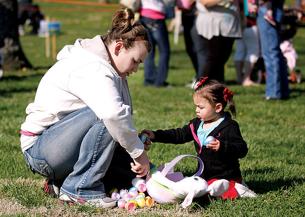 Brittany Martone goes through Easter eggs that her daughter, Gabriella, picked up at the Colgate Park Easter egg hunt on Saturday. Children got candy and had a chance to win special gift baskets with a golden egg. Staff photo by Jerod Clapp