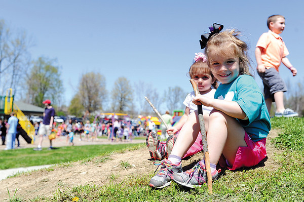 Sisters Olivia, 4, and Addison Rough, 1, sit on a mound by the Vissing Park playground while waiting for the Helicopter Easter Egg Drop to begin in Jeffersonville Saturday afternoon. <br /> Staff photo by Tyler Stewart