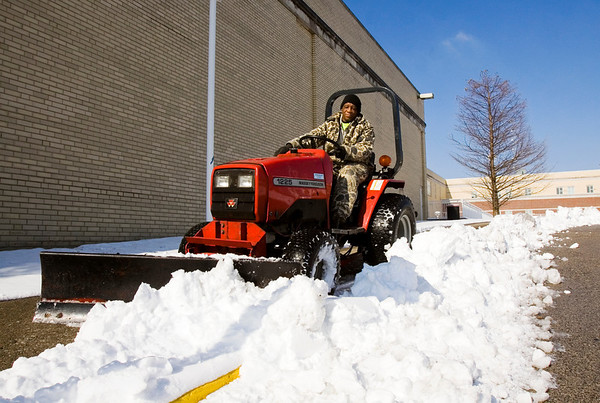 Groundskeeper Wilson Newbolt, New Albany, clears snow from a sidewalk at New Albany High School on Monday morning. According to the National Weather Service, there will be a high near 37 on Tuesday with a chance of mixed precipitation. Staff photo by Christopher Fryer