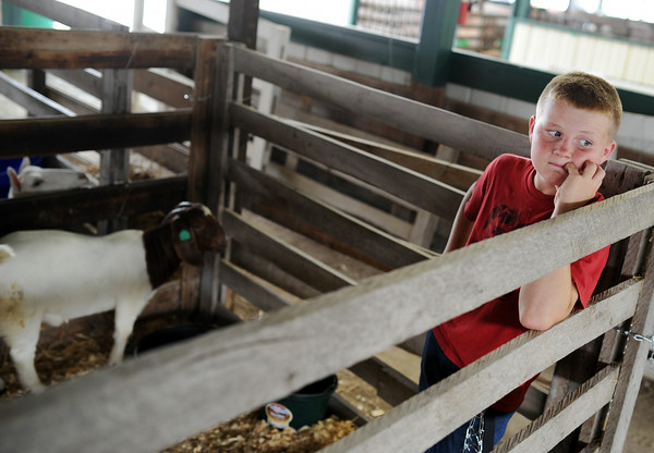 Dylan Johnson, 13, waits with his boar goats in the stables of the Clark County 4-H fairgrounds Saturday. This is Dylan's first year showing goats at the 4-H, and hoped to sell one of the two on Sunday.<br /> Staff photo by Tyler Stewart