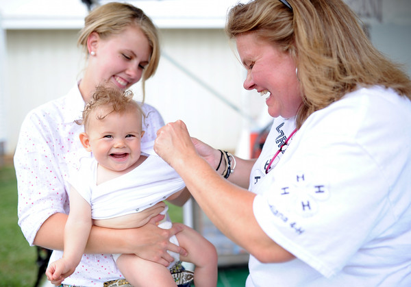 Owen Cristiani-Hunt, 7 months, is all smiles as his mother, Rachel Cristiani, and grandmother, Anne Cristiani, put on his onesie. Owen was awarded the blue ribbon in the 6-12 month category of the Clark County 4-H Baby Fair.<br /> Staff photo by Tyler Stewart