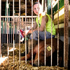 Calvin Mullins, 9, Marysville, takes a moment to spend time with his swine, Clark, in his pen at the Clark County 4-H fairgrounds Thursday morning. Despite having two surgeries to remove a tumor larger than a softball on his spine in June, Mullins was eager make his debut showing swine at the 4-H. <br /> Staff photo by Tyler Stewart