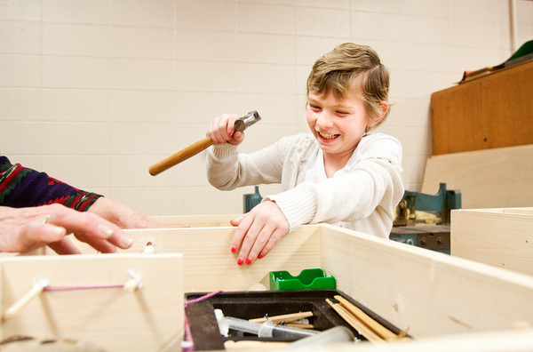 Madaleine Reed, 8, Sellersburg, shares a laugh with her grandmother, Linda Reed, Charlestown, while they work on their found object assemblage during a Jeffersonville Arts Alliance JAM Session in the wood shop at River Valley Middle School in Jeffersonville on Saturday. Their piece will be a part of a larger assemblage installation, created in the style of works by the late sculptor Louise Nevelson, that will be put on display in the main lobby at Clark Memorial Hospital. Staff photo by Christopher Fryer