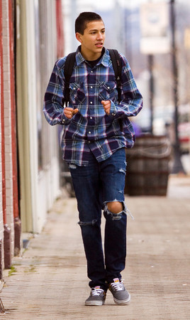 Kevin Taylor, 15, walks along Pearl Street on the way to his grandmother's house in downtown New Albany on Thursday afternoon. Staff photo by Christopher Fryer