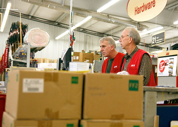 Jim and Gary Staashelm, managers at the Ace Hardware store on Charlestown Road in New Albany, review some orders on Thursday. Gary said some customers are buying incandescent bulbs in bulk, like the order of 15 cases in the foreground. Staff photo by Jerod Clapp