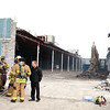 Officers from the Clarksville Fire Department talk after responding to a fire at the former Value City property along Eastern Boulevard — the construction site of the New Tech school at Clarksville Community Schools — on Wednesday. Alan Muncie, principal owner of ARC Construction Management, said while the construction crew was cutting joists, embers fell into a large debris pile that included insulation, which caused it to ignite. After demoltion crews put water on it, firemen extinguished the pile. Clarksville Fire Marshall Brent Wilson said no injuries were reported and there was no apparent damage to the structure, but a more thorough investigation of the site had yet to be completed. Staff photo by Jerod Clapp