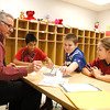 Mike Carter, grandfather of a Borden Elementary School student, works his station for the school's first Math Superbowl with Dads. Miguel Huerta, Kaden Holmes and Caitlyn Cook worked on their math skills along with the rest of the fourth-grade class. Staff photo by Jerod Clapp