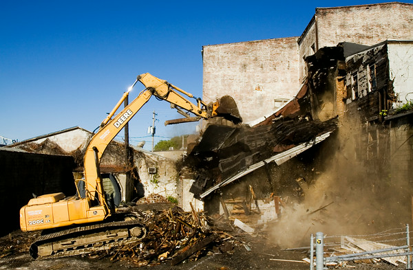 Tom Robinson, Galena, with Merrel Bierman Excavating out of Clarksville, uses an excavator to demolish part of the old Reisz Furniture building along Main Street in downtown New Albany on Tuesday morning. Local developer Ron Carter plans to turn the property into office, retail and residential space. Staff photo by Christopher Fryer