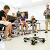 YMCA of Southern Indiana Floyd County Branch summer campers look on as  Joe Dues, a mechanical engineering technology professor, demonstrates the operation of a robot outfitted with Mechanum wheels during a visit to the Purdue University College of Technology in New Albany on Thursday morning. Staff photo by Christopher Fryer