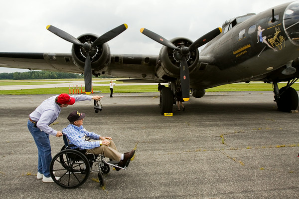"World War II veteran Kenneth Payton, 93, and his son-in-law, David Gibson, both of Louisville view the exterior of a B-17 bomber on display at the Clark County Airport along U.S. 31 as part of The Liberty Foundation's 2014 Salute to Veterans tour. The plane, which dates back to 1945, was used in the 1990 film ""Memphis Belle"", and is one of only 12 B-17 bombers in the world that are still able to fly. Staff photo by Christopher Fryer"