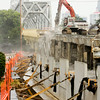 An excavator outfitted with a jack hammer is pictured on the Clark Memorial Bridge as crews work to dismantle the Indiana approach to the structure in Jeffersonville on Tuesday morning. The bridge will be completely shut down for about six weeks. Staff photo by Christopher Fryer