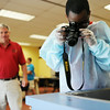 Aikas Speed, 12, Charlestown, takes a photo of a bloody hand print on the countertop while Detective Donnie Bowyer watches over during a mock crime scene investigation at the Charlestown Public Library Wednesday.<br /> Staff photo by Tyler Stewart