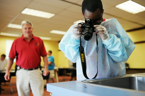 Aikas Speed, 12, Charlestown, takes a photo of a bloody hand print on the countertop while Detective Donnie Bowyer watches over during a mock crime scene investigation at the Charlestown Public Library Wednesday. Staff photo by Tyler Stewart