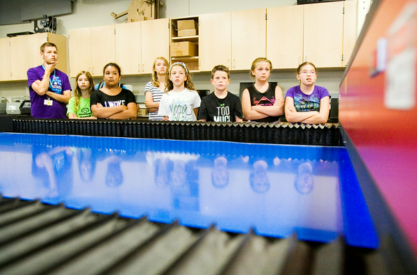 YMCA of Southern Indiana Floyd County Branch summer campers listen to a description of a laser machine in the Manufacturing Lab at the Purdue University College of Technology in New Albany on Thursday morning. Staff photo by Christopher Fryer